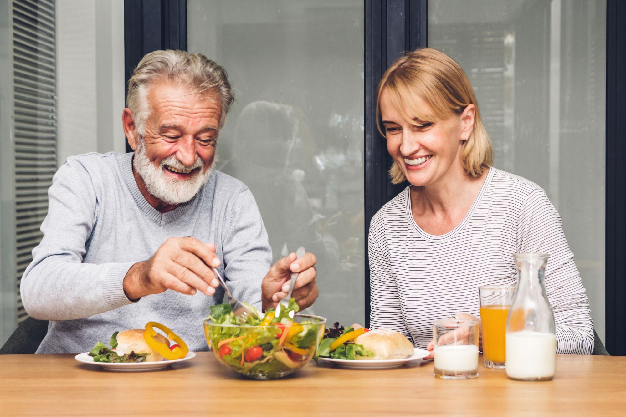 To eldre spiser salat sammen. Foto