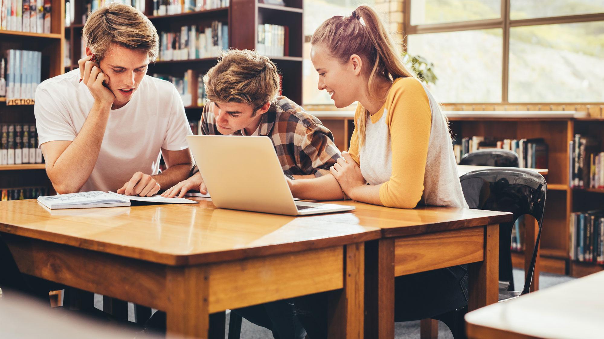 Ungdommer studerer på biblioteket. Foto