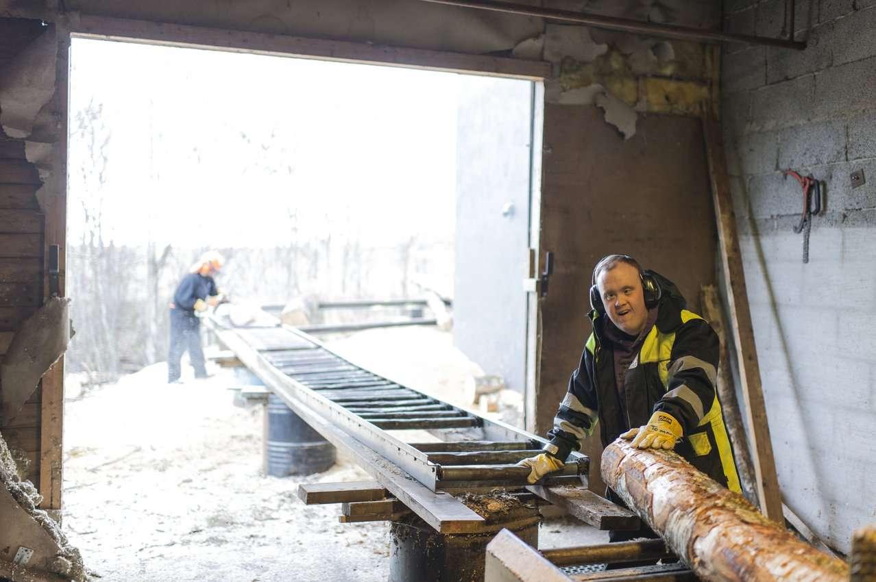 Mann med utviklingshemming som jobber på sageri. Foto.