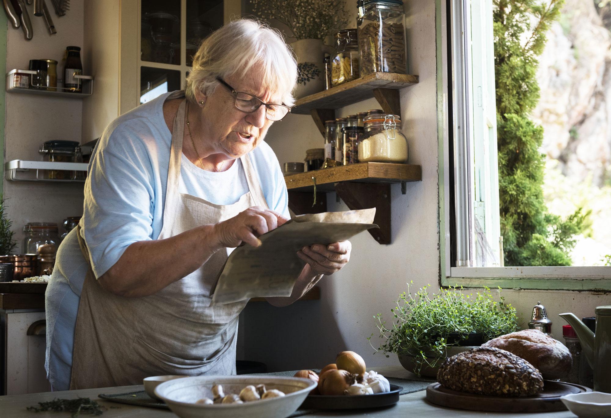 Eldre dame står på kjøkkenet og leser matoppskrift. Foto
