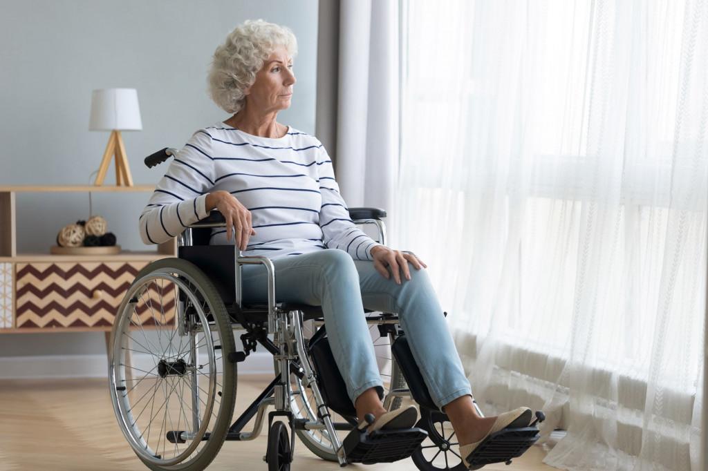 Dame sitter i rullestol og ser ut av vinduet