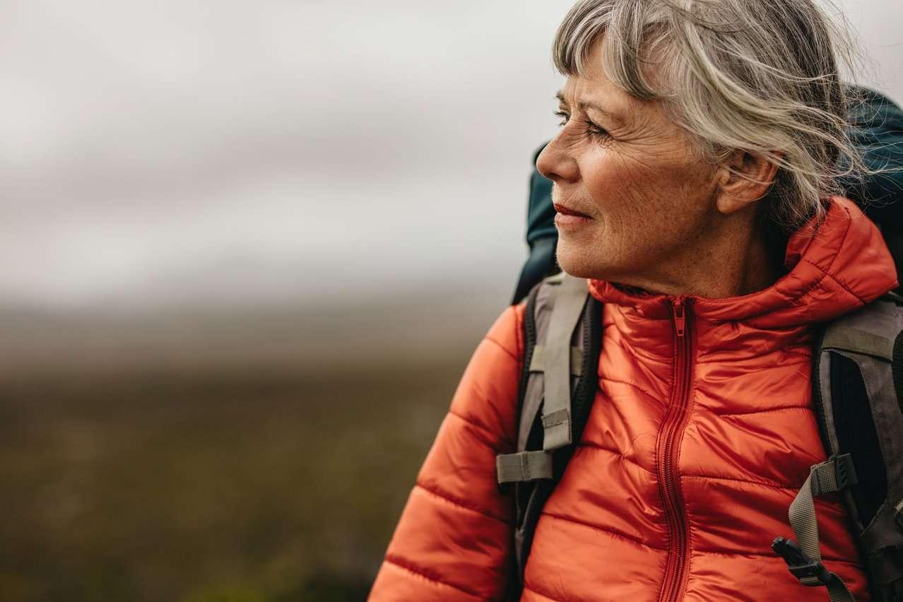 Eldre dame ser tenkende ut i horisonten. Foto