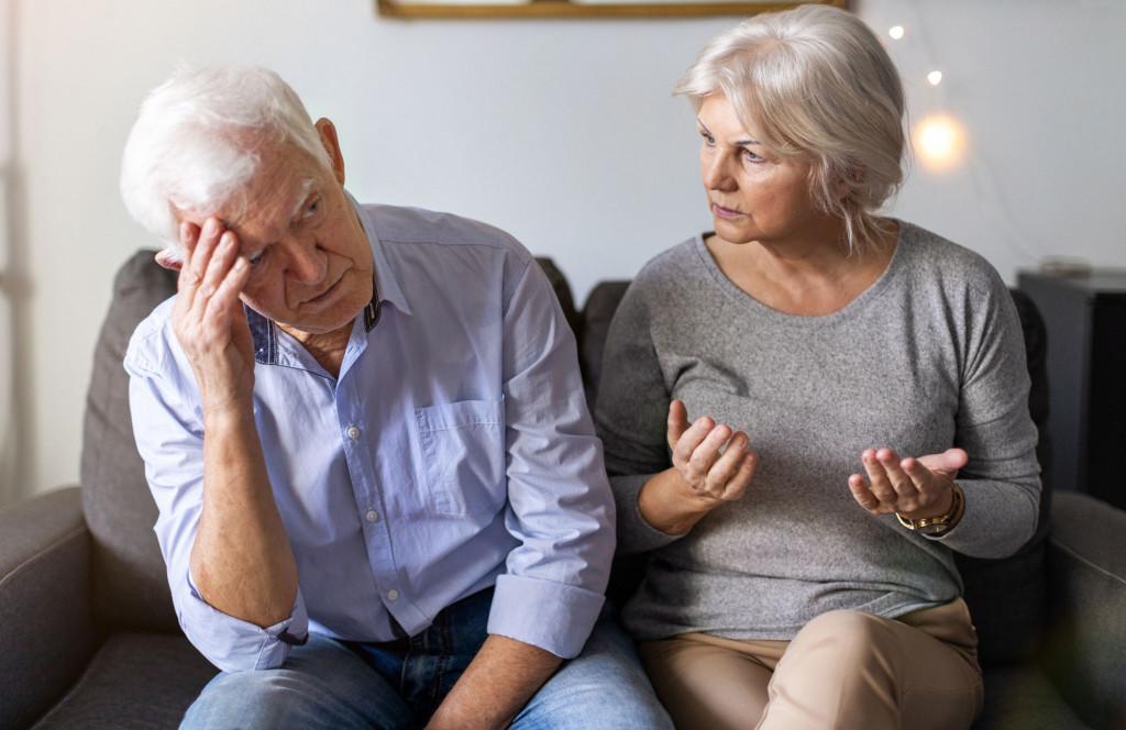 Eldre par sitter i sofa og diskuterer. Foto