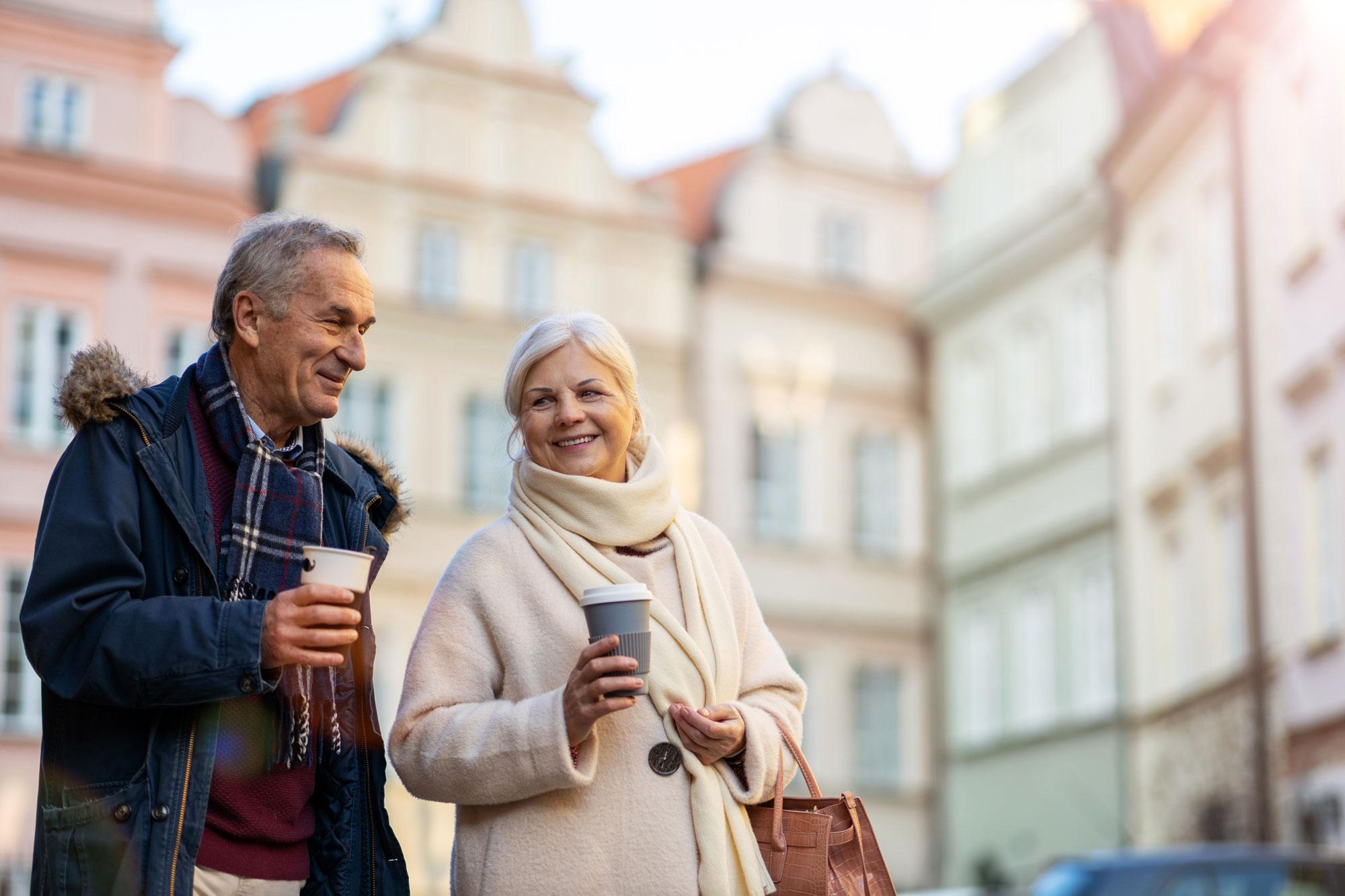 Eldre par går tur i en by med en kopp kaffe. Foto