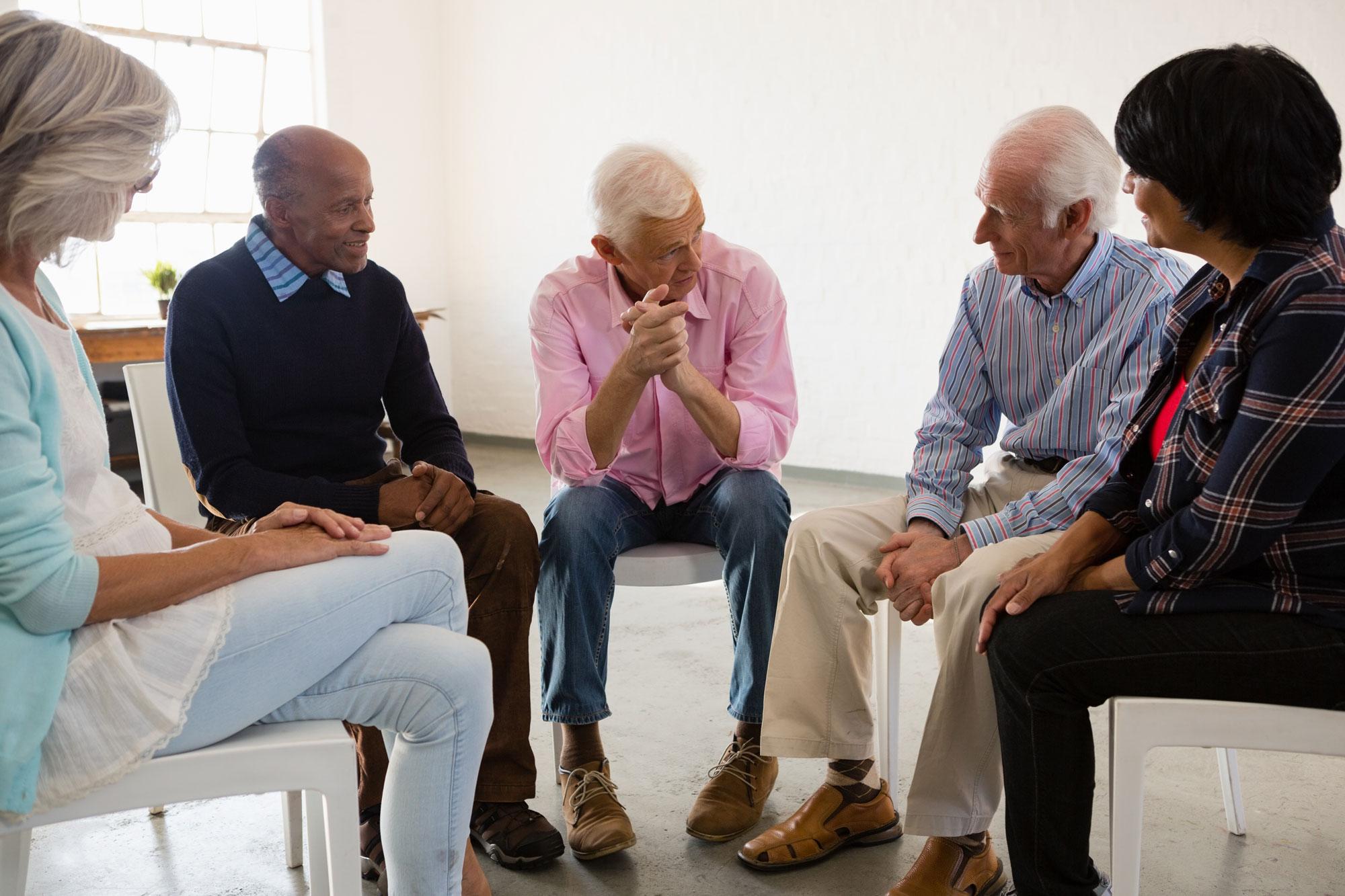 Eldre mennesker sitter i en ring og snakker