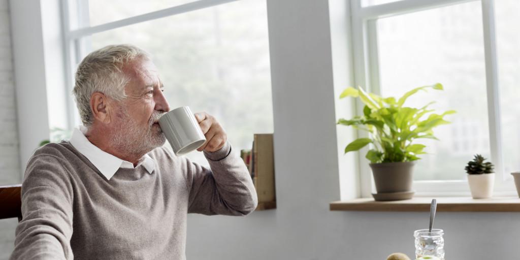 Mann ser ut av vinduet og drikker kaffe. Foto