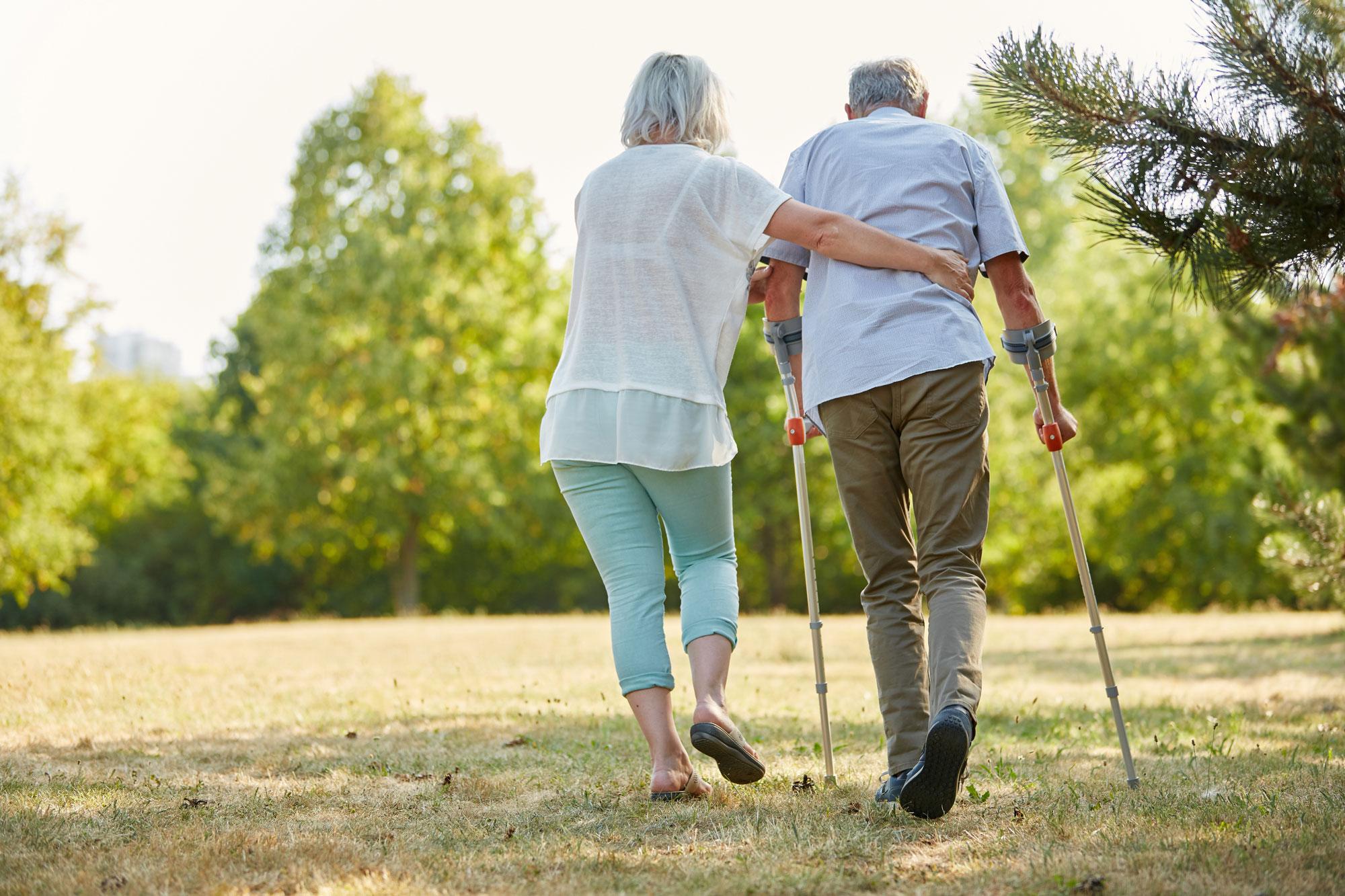 Kvinne hjelper mann med krykker på tur