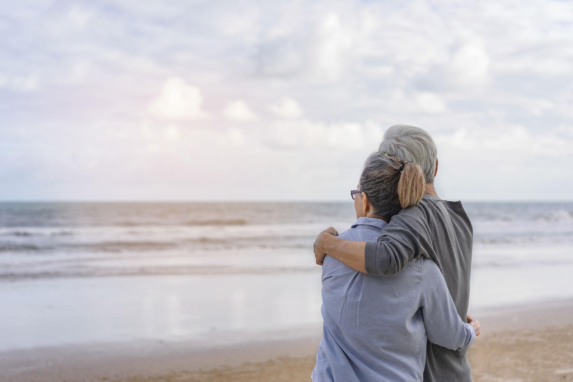 Par står ved vannkanten og ser utover havet. Foto