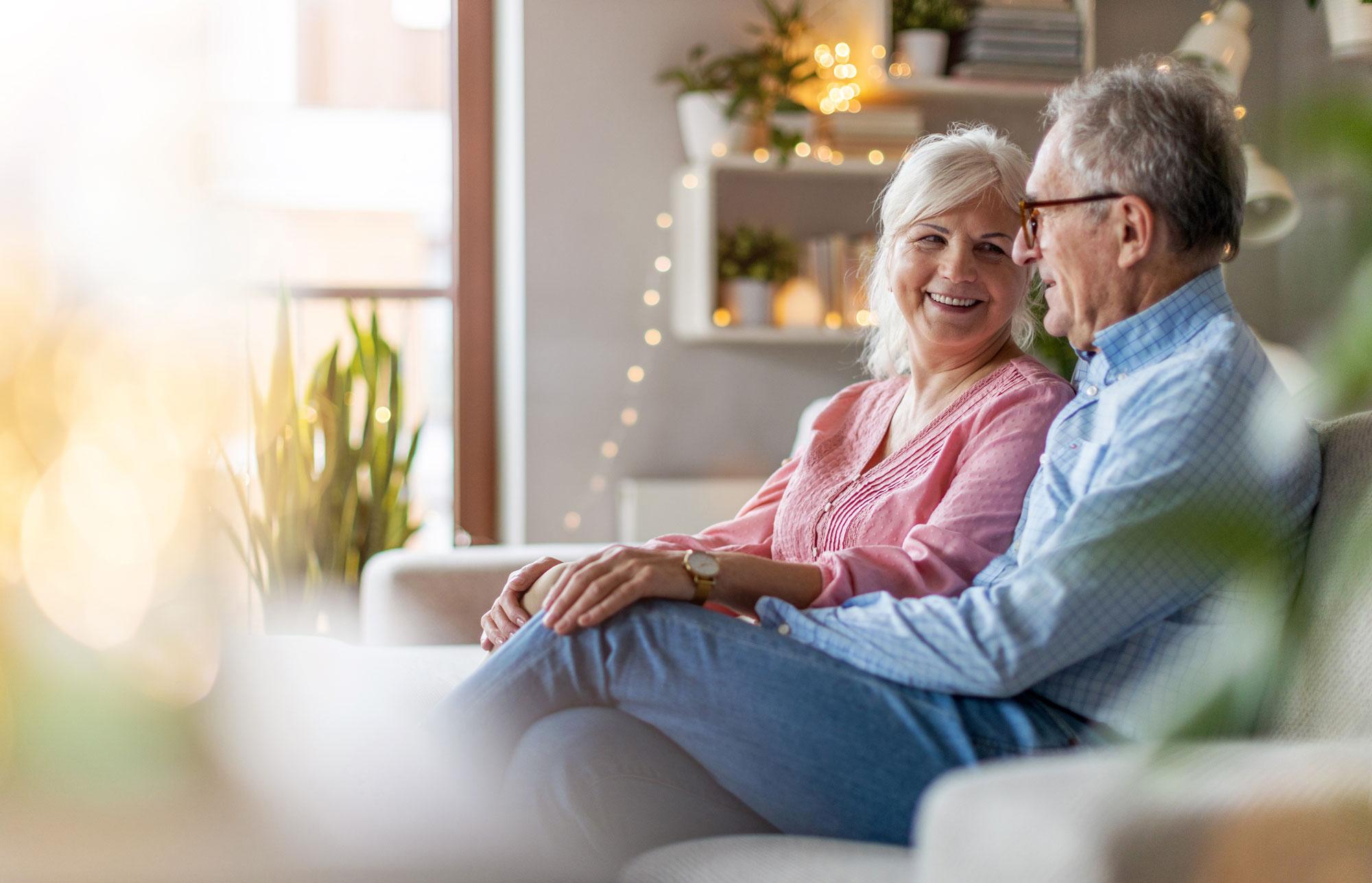 Eldre par sitter i sofaen hjemme og snakker. Foto