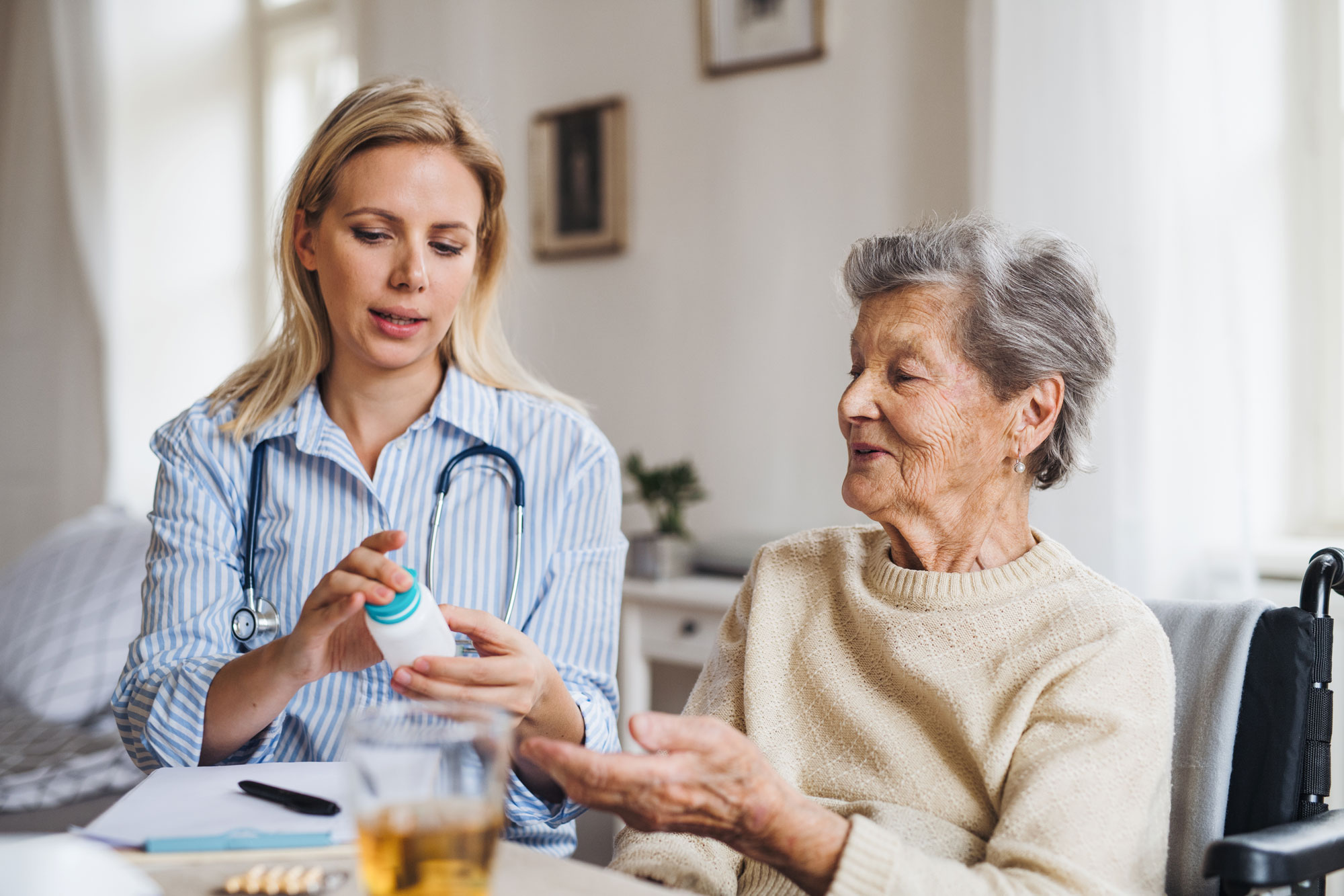 Pleier gir medisin til eldre dame. Foto.