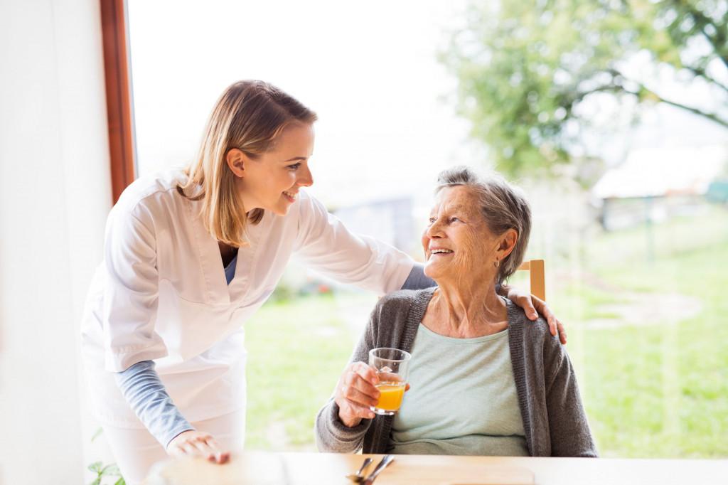 Pleier og eldre dame snakker sammen. Foto