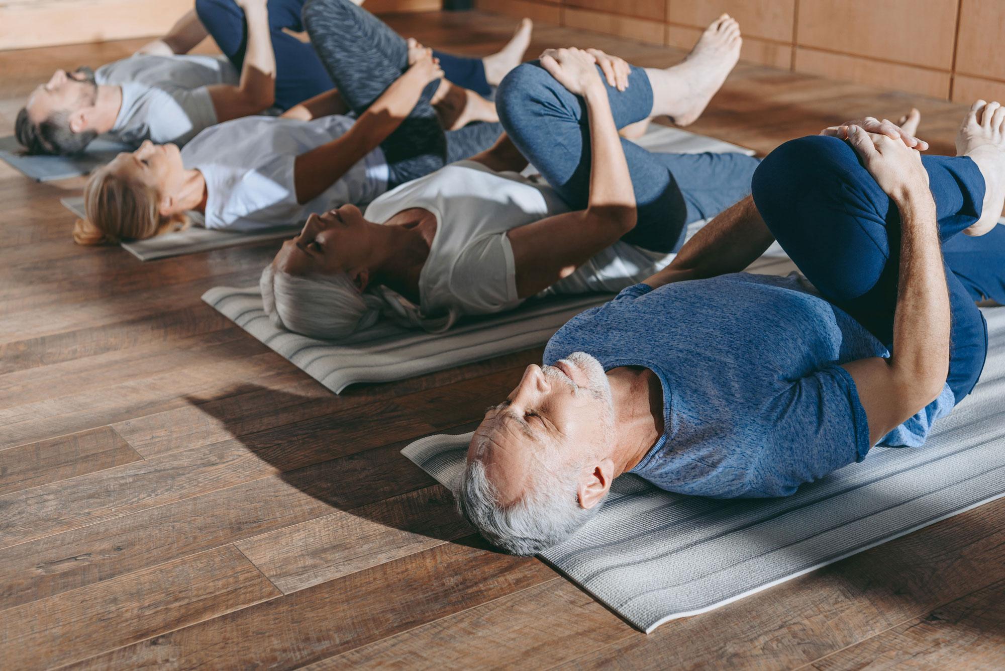 Eldre mennesker ligger på matte og gjør øvelser. Foto