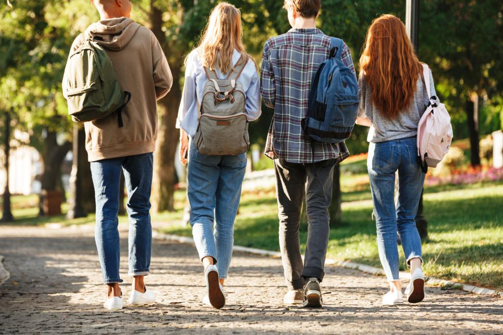 Fire ungdommer går bortover veien. Foto