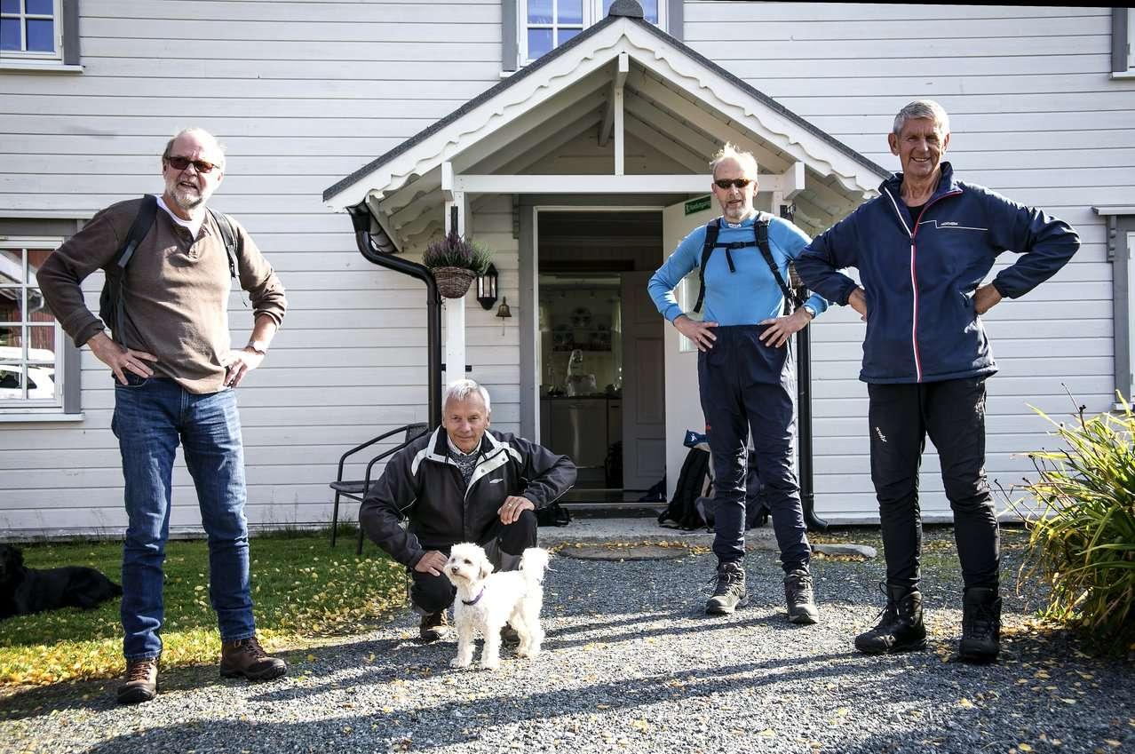 Fire menn og en hund står foran et hus. Foto