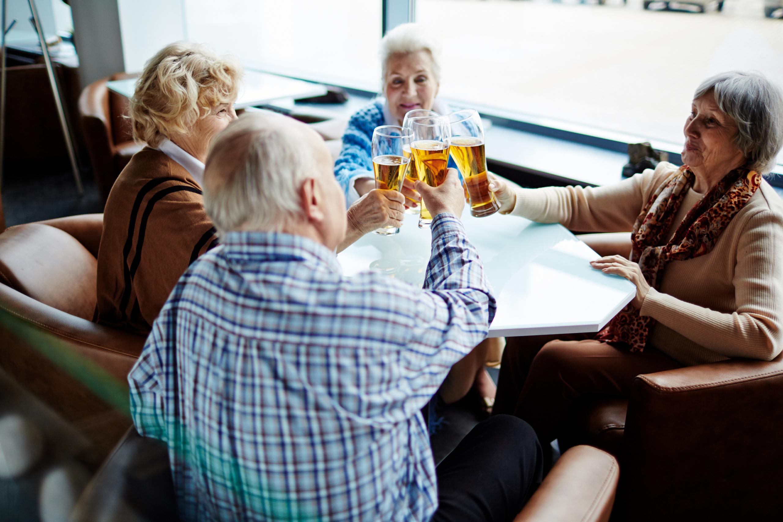 Eldre mennesker skåler i øl. Foto