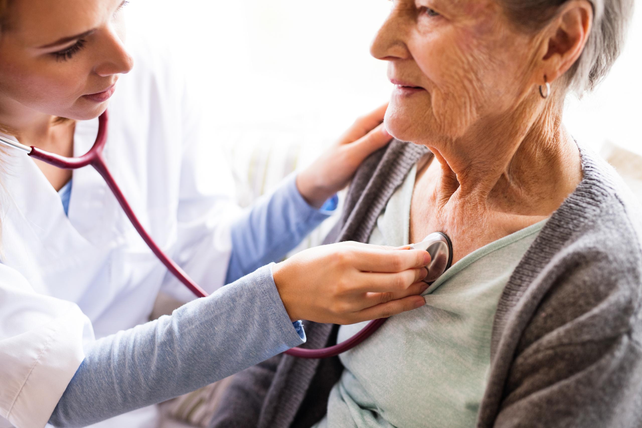 Lege lytter på hjertet til eldre dame. Foto