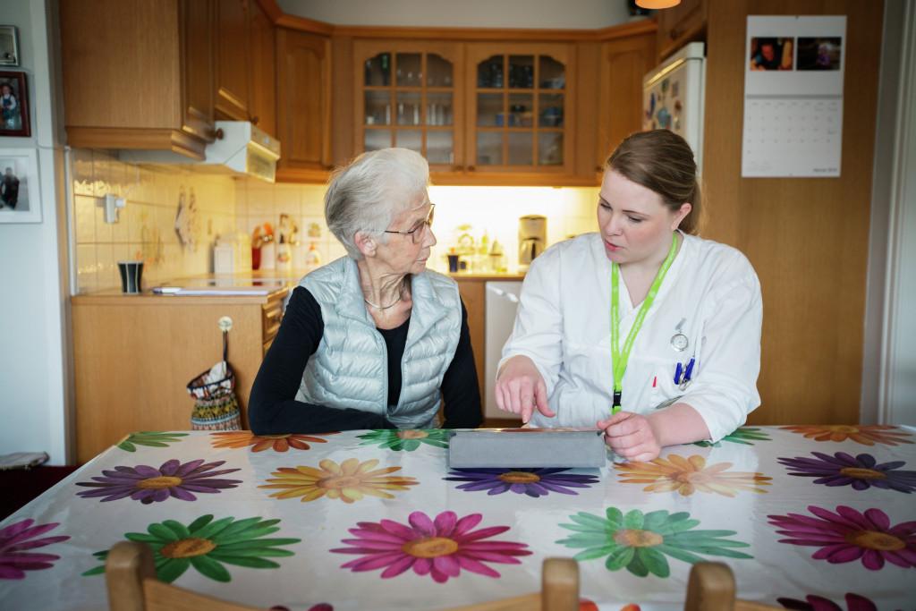 Eldre damer snakker med pleier. Foto