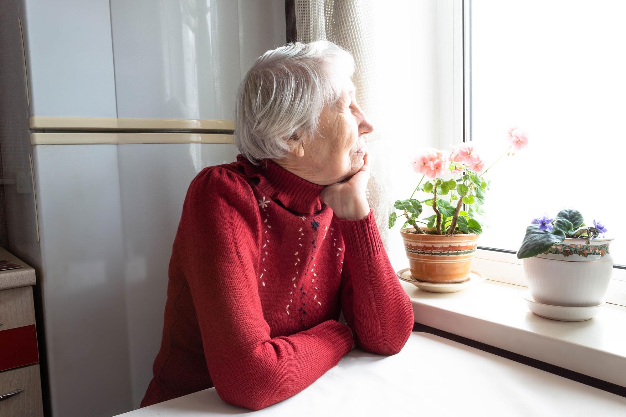 Eldre dame ser ut av vinduet og tenker. Foto