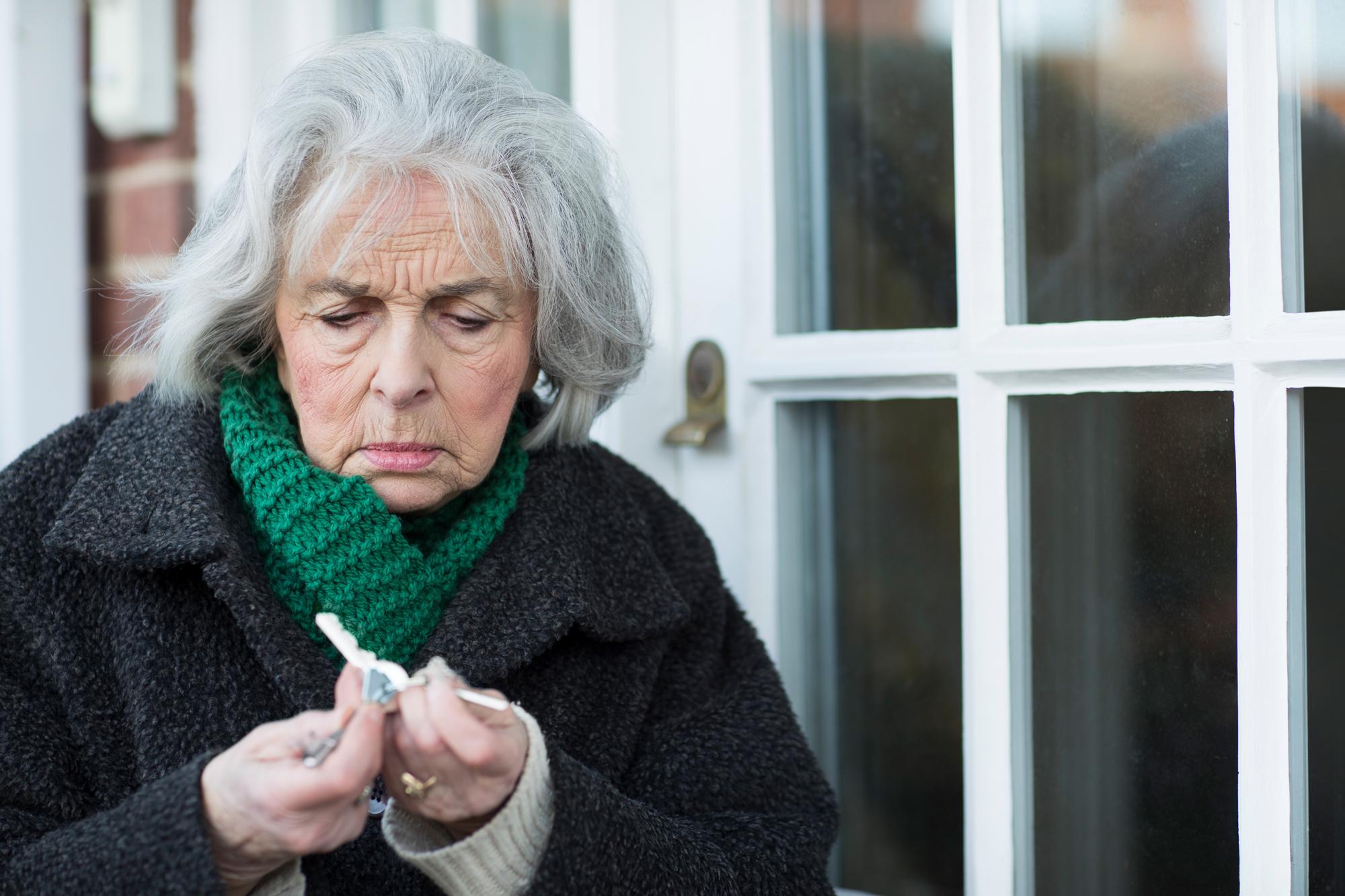 Dame står forvirret med nøkkelknippet til huset. Foto
