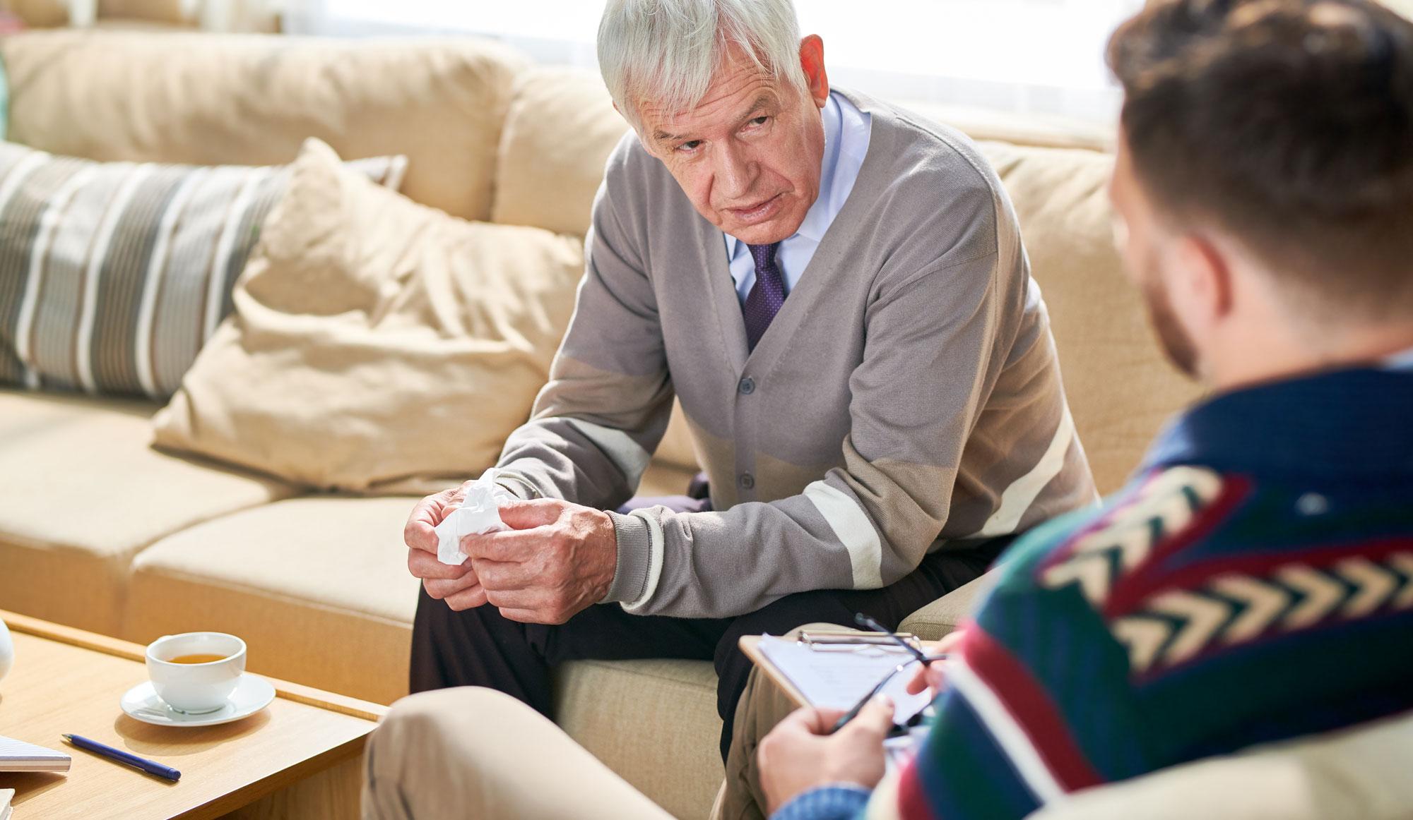 Eldre mann snakker med en psykolog. Foto