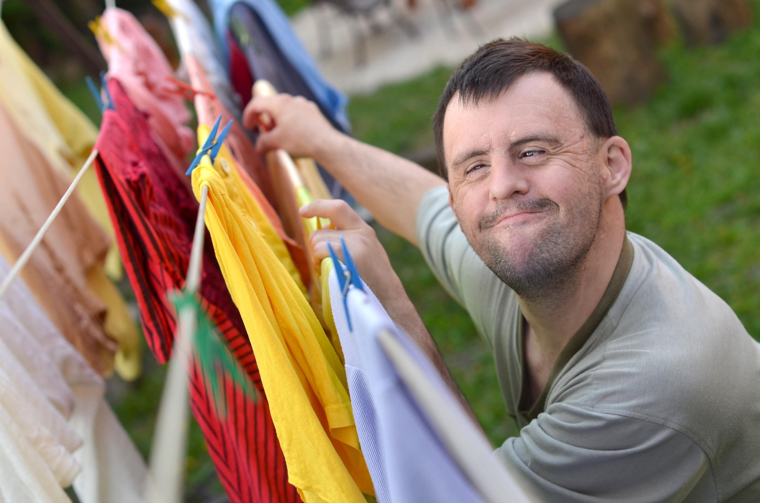 Person med downs henger opp klesvask. Foto
