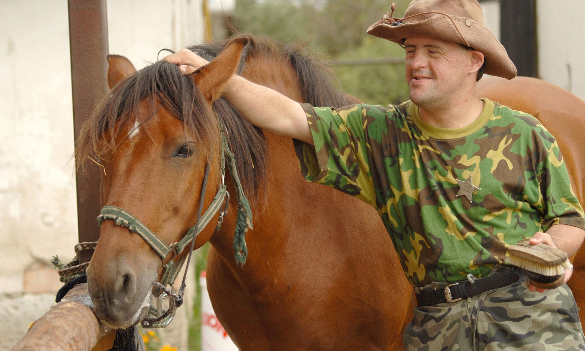 Mann med downs klapper hest. Foto