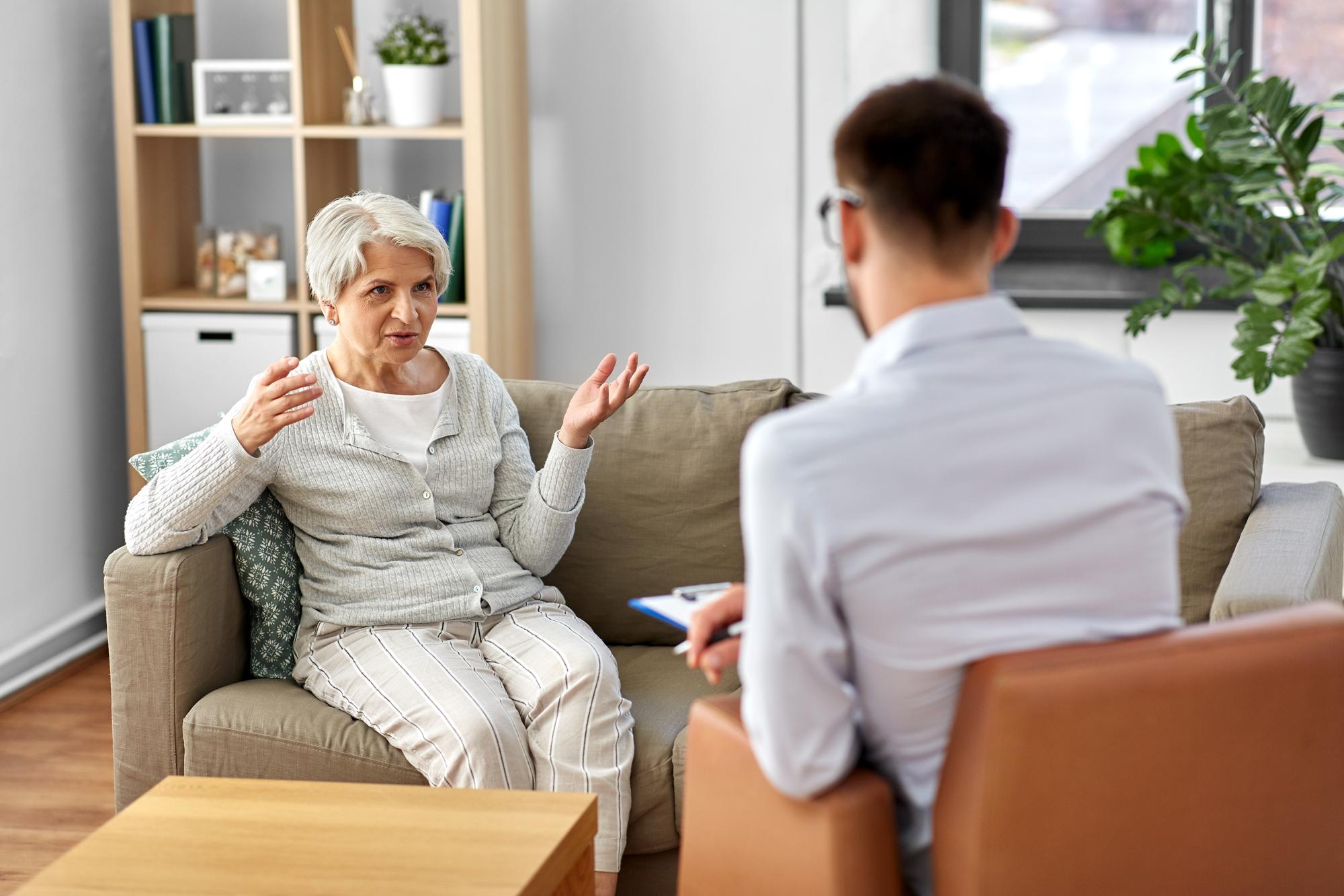 Eldre dame sitter hos psykologen. Foto