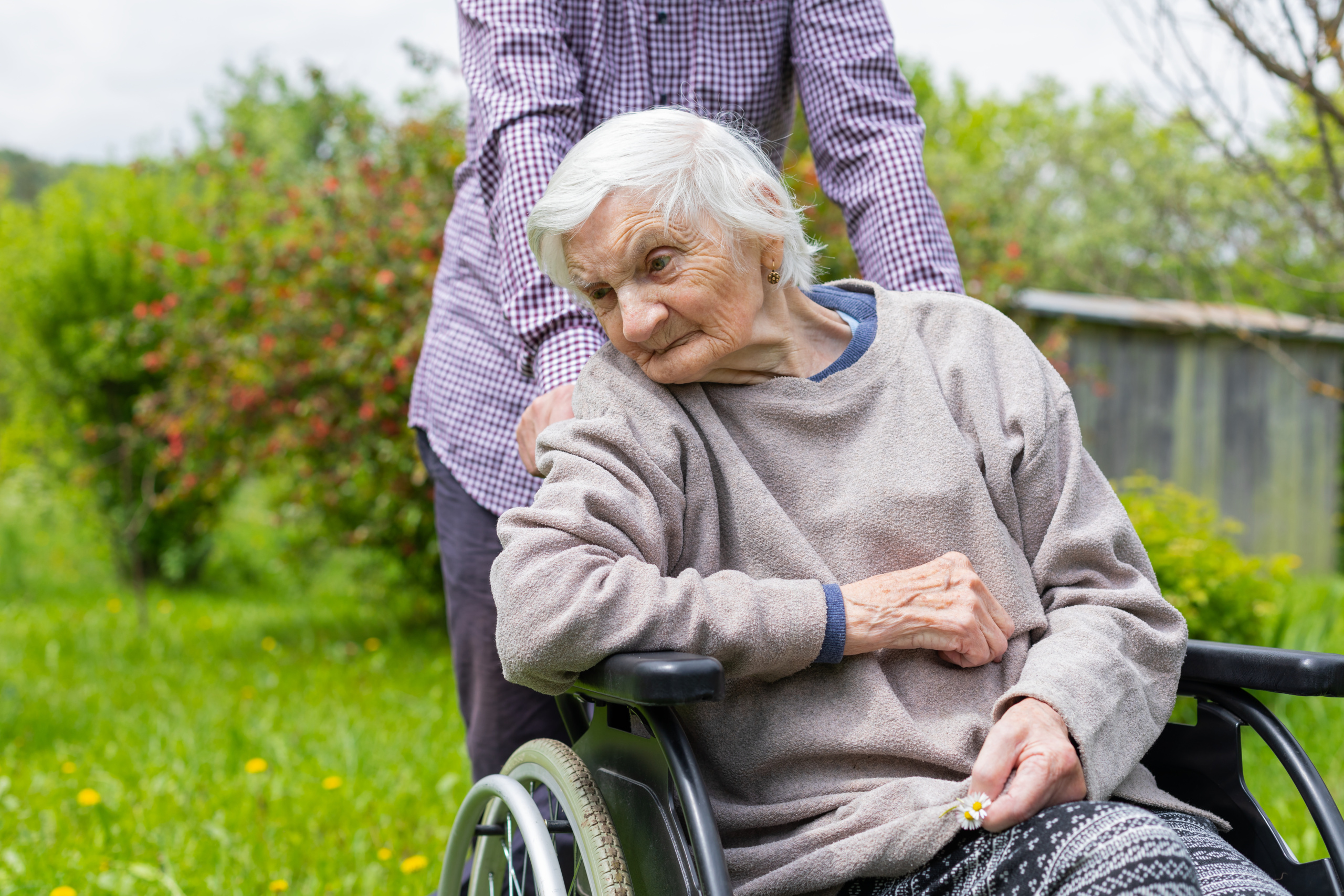 Eldre dame sitter i rullestol. Foto
