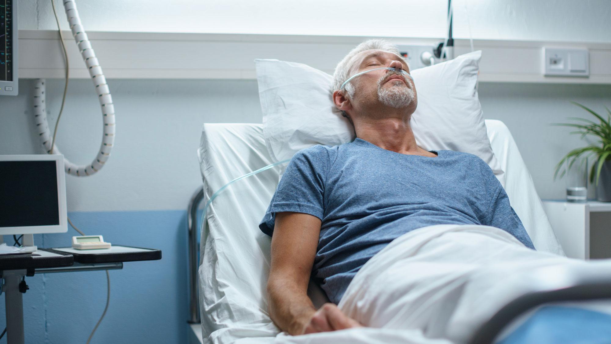 Eldre mann ligger i seng på sykehus. Foto
