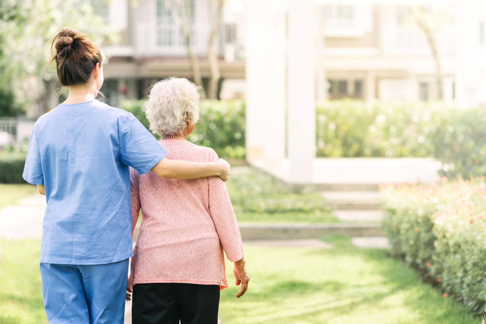 Helsefagarbeider holder rundt eldre kvinne. Foto