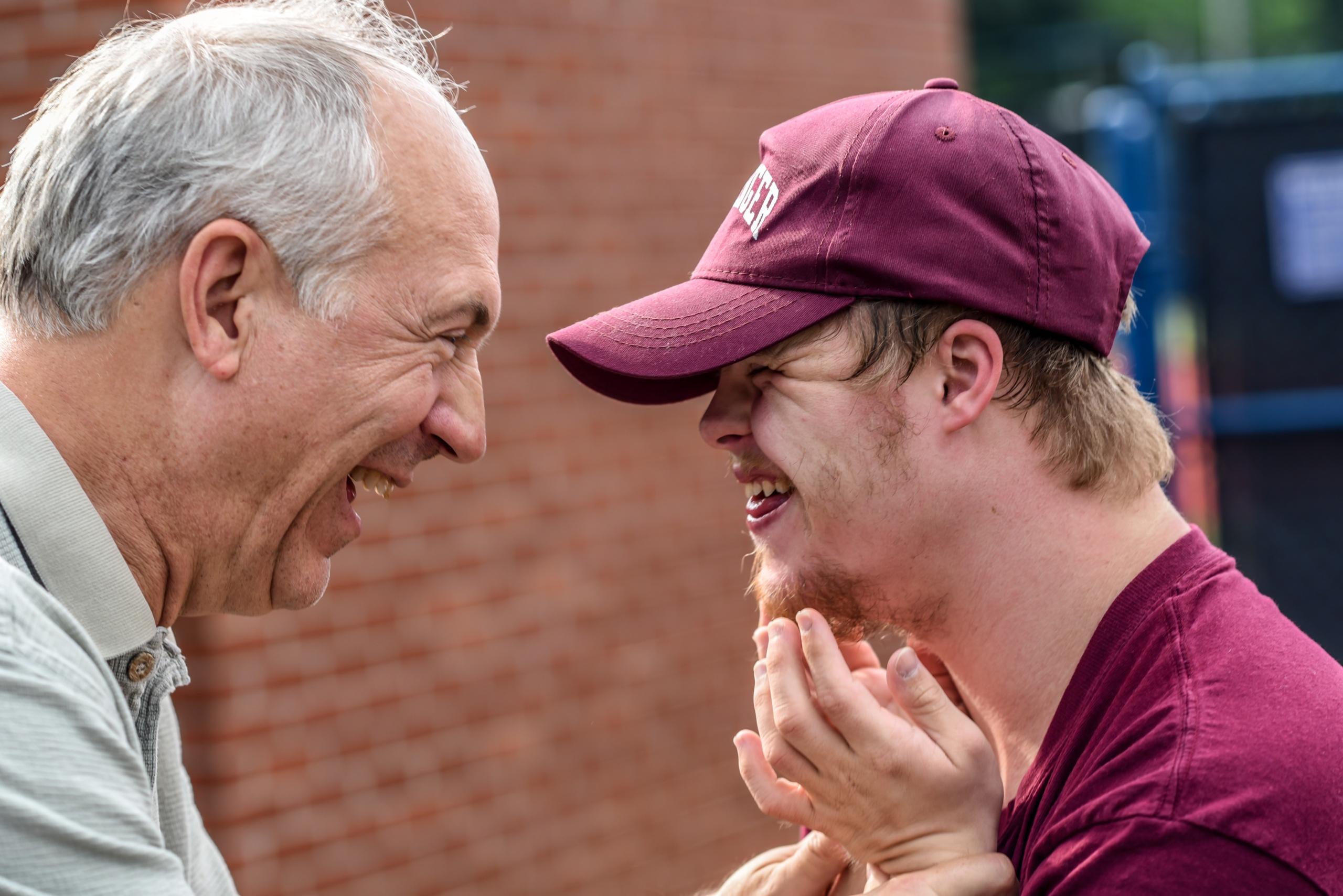 Far og sønn ser på hverandre og ler