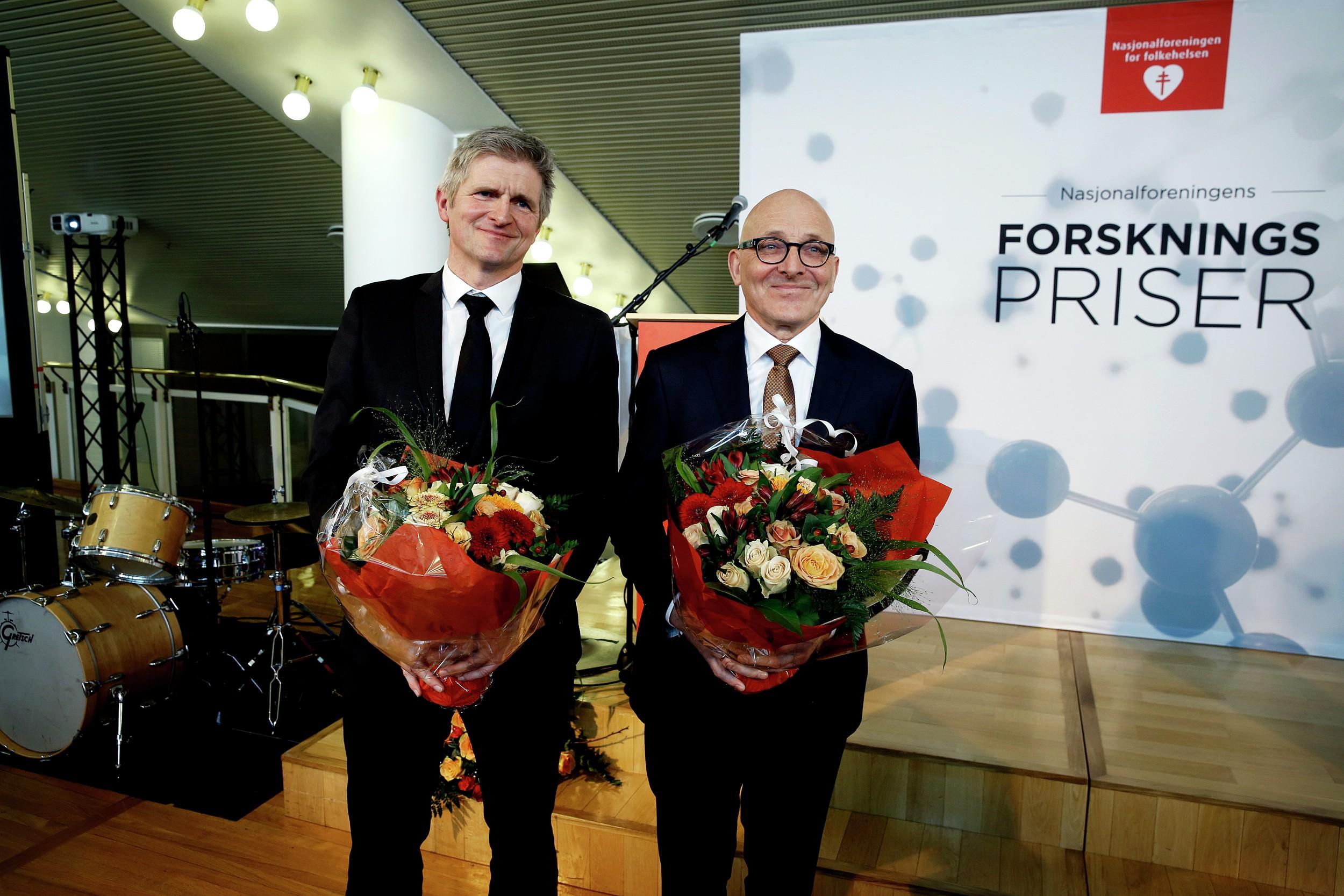 Geir Selbæk og Kaare Bønaa står med en blomsterbukett etter å ha mottatt Nasjonalforeningesn forskningspriser. Foto