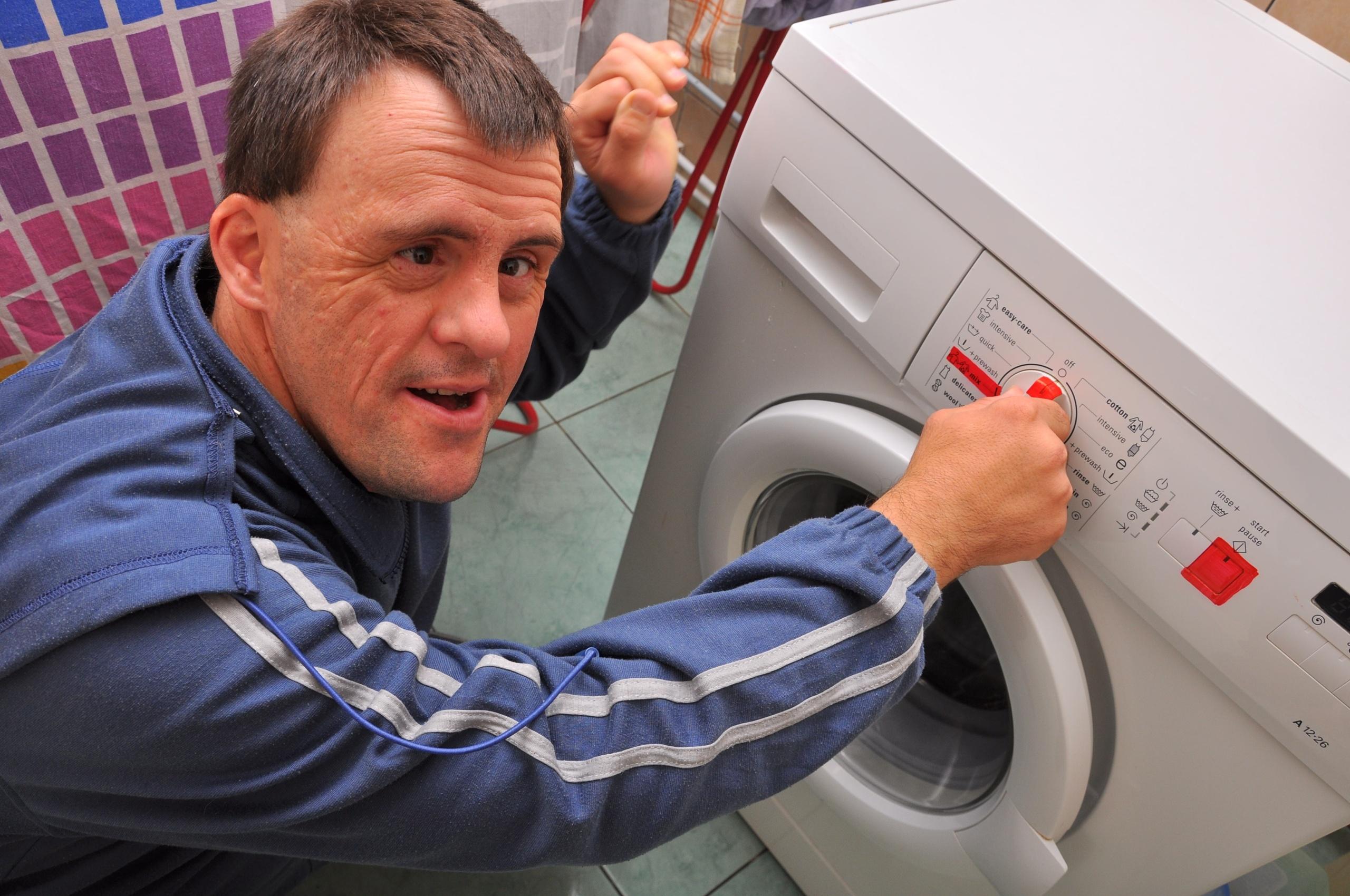 Mann med downs setter på vaskemaskinen. Foto