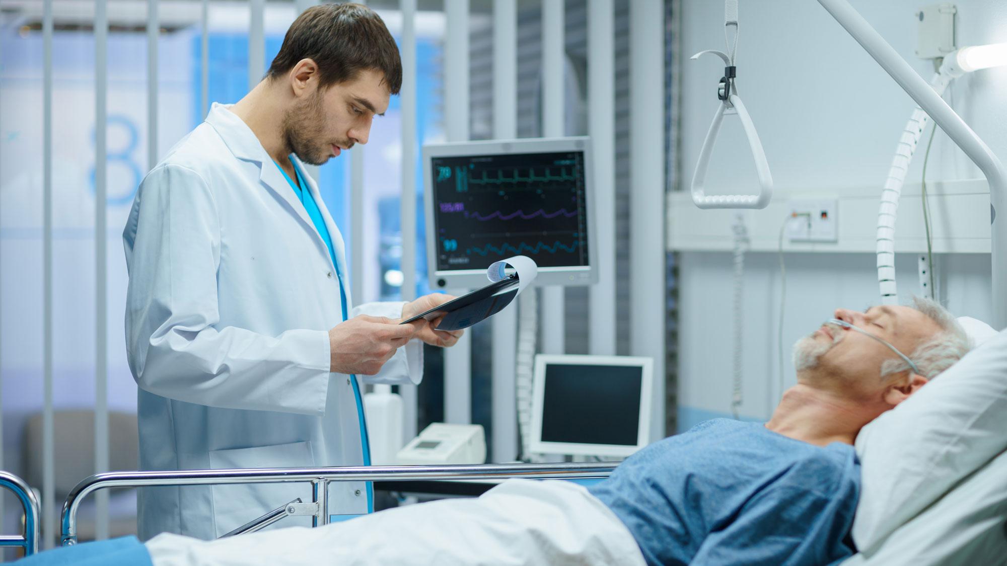 Lege står foran eldre mann på hospitalet og observerer. Foto