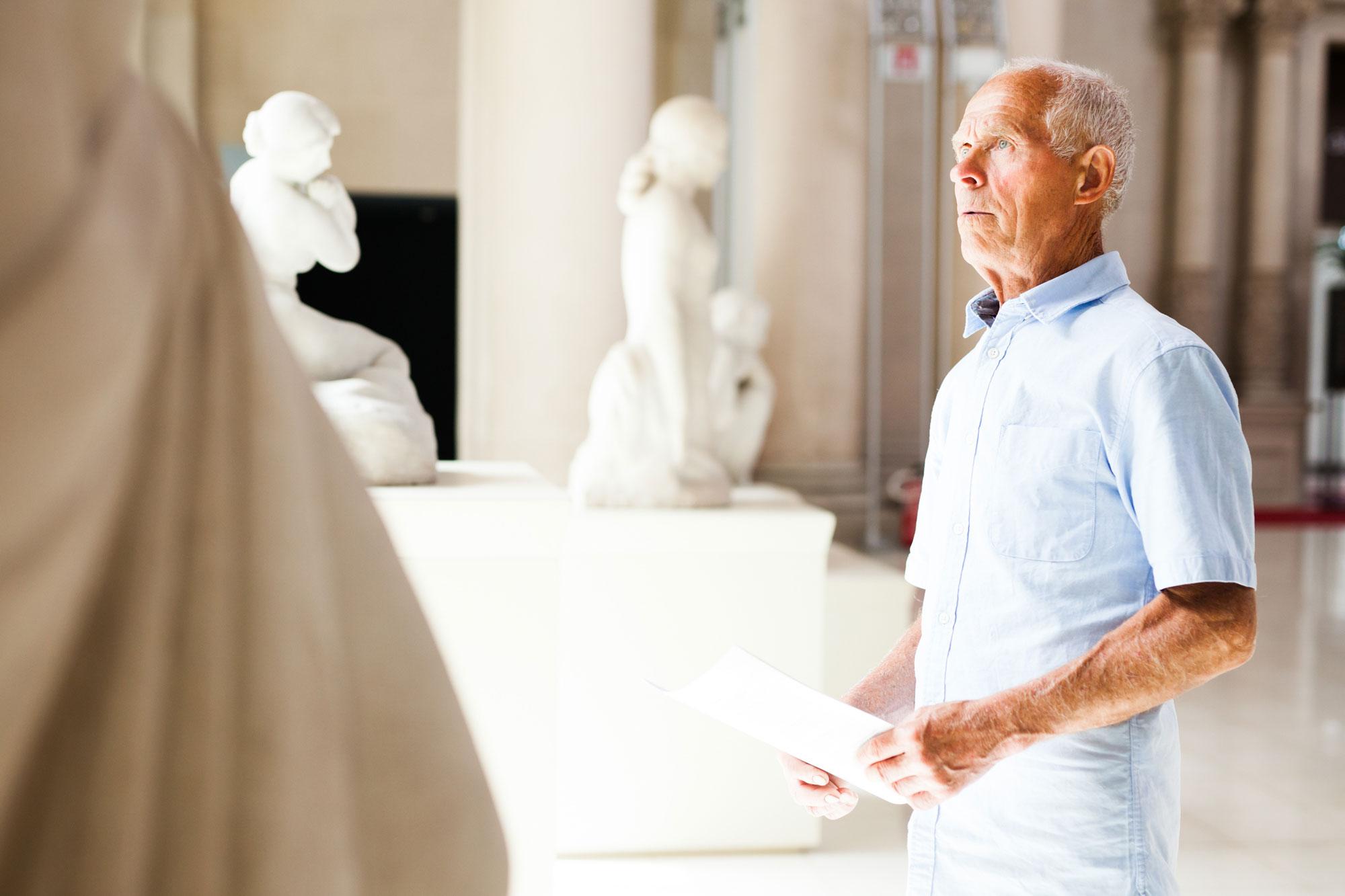 Eldre mann ser på skulpturer. Foto