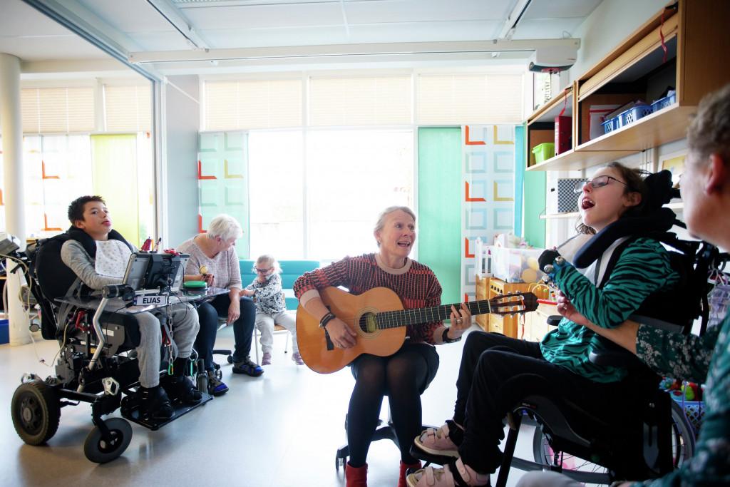 Musikk og gitar foran personer med utviklingshemning. Foto