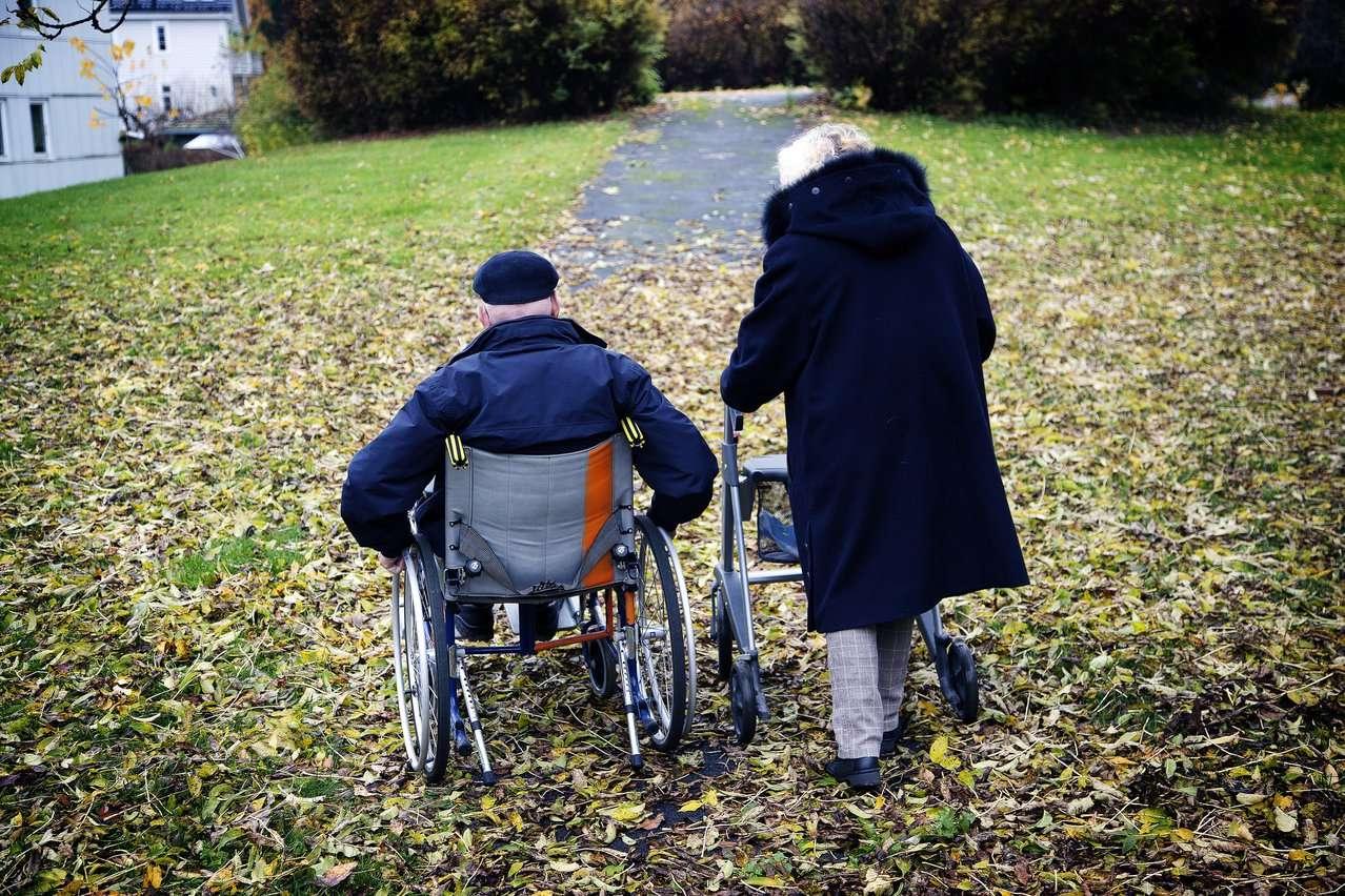 En dame med rullator og en mann i rullestol på tur i parken. Foto.
