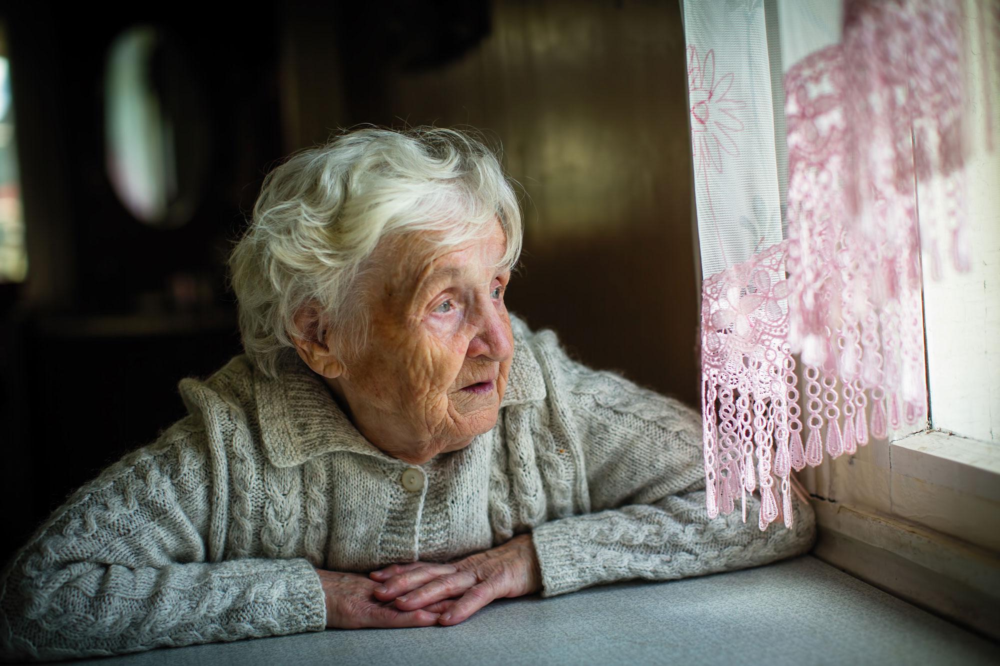 Eldre dame ser ut av vinduet. Foto