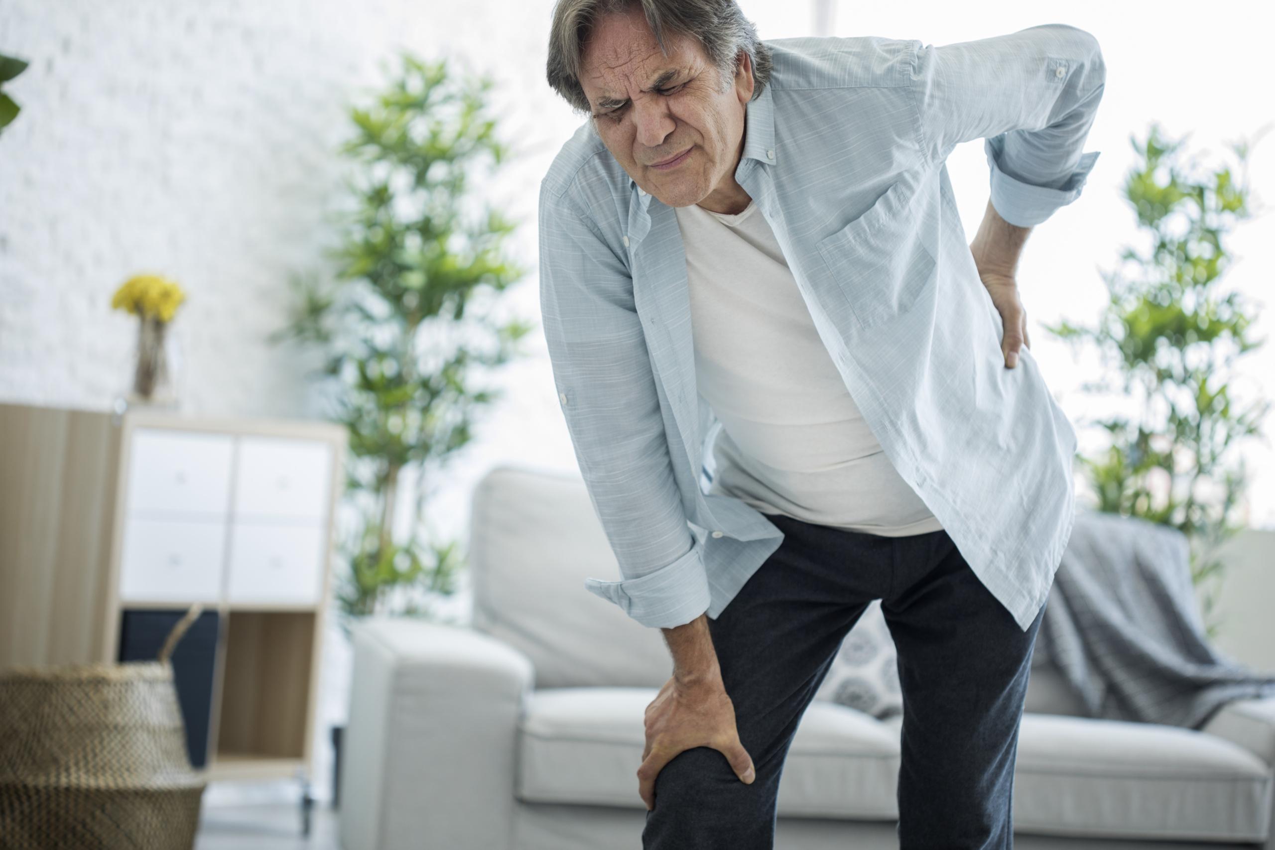 Mann bøyer seg fremover med smerter i ryggen. Foto
