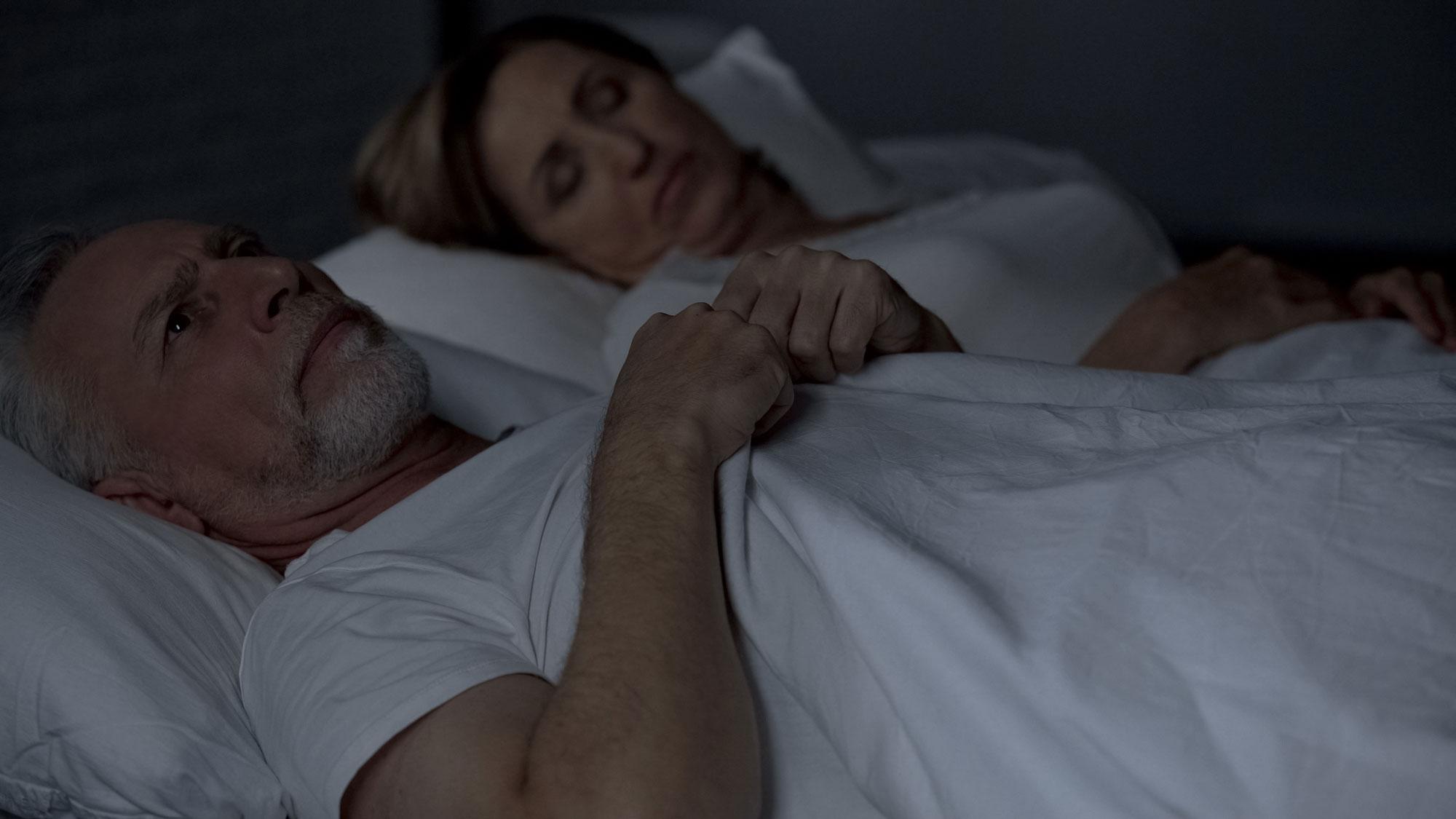 Mann ligger i sengen og får ikke sove. Foto