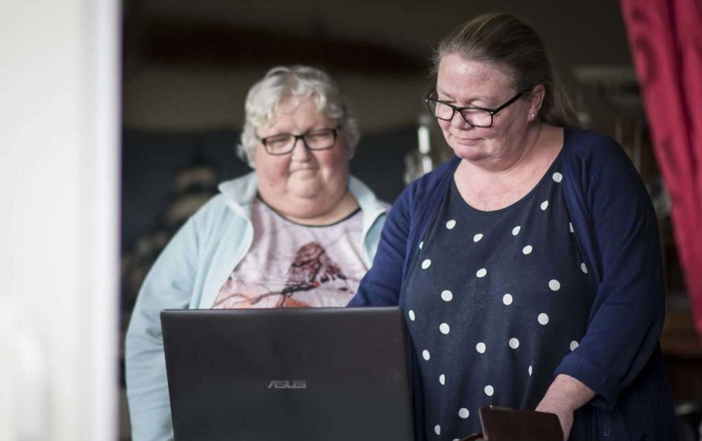 Kvinne og person med utviklingshemning ser på skjerm. Foto.