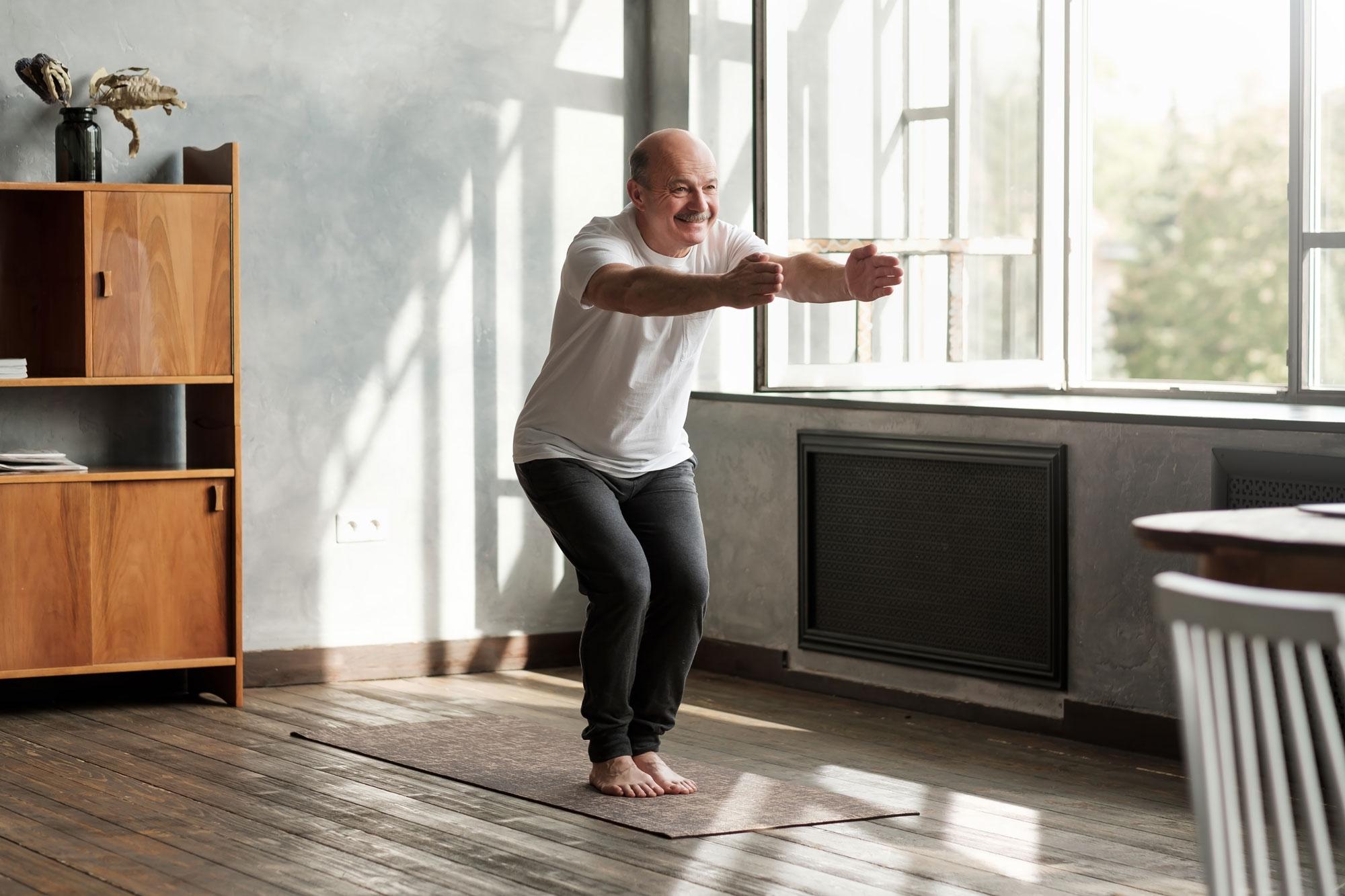 Eldre mann gjør øvelser i stua. Foto
