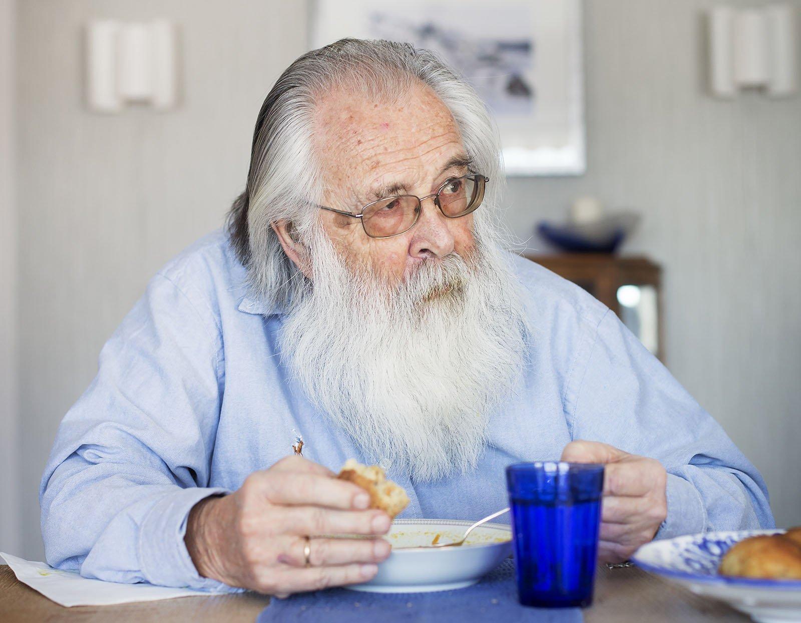 Mann med skjegg spiser. Foto.