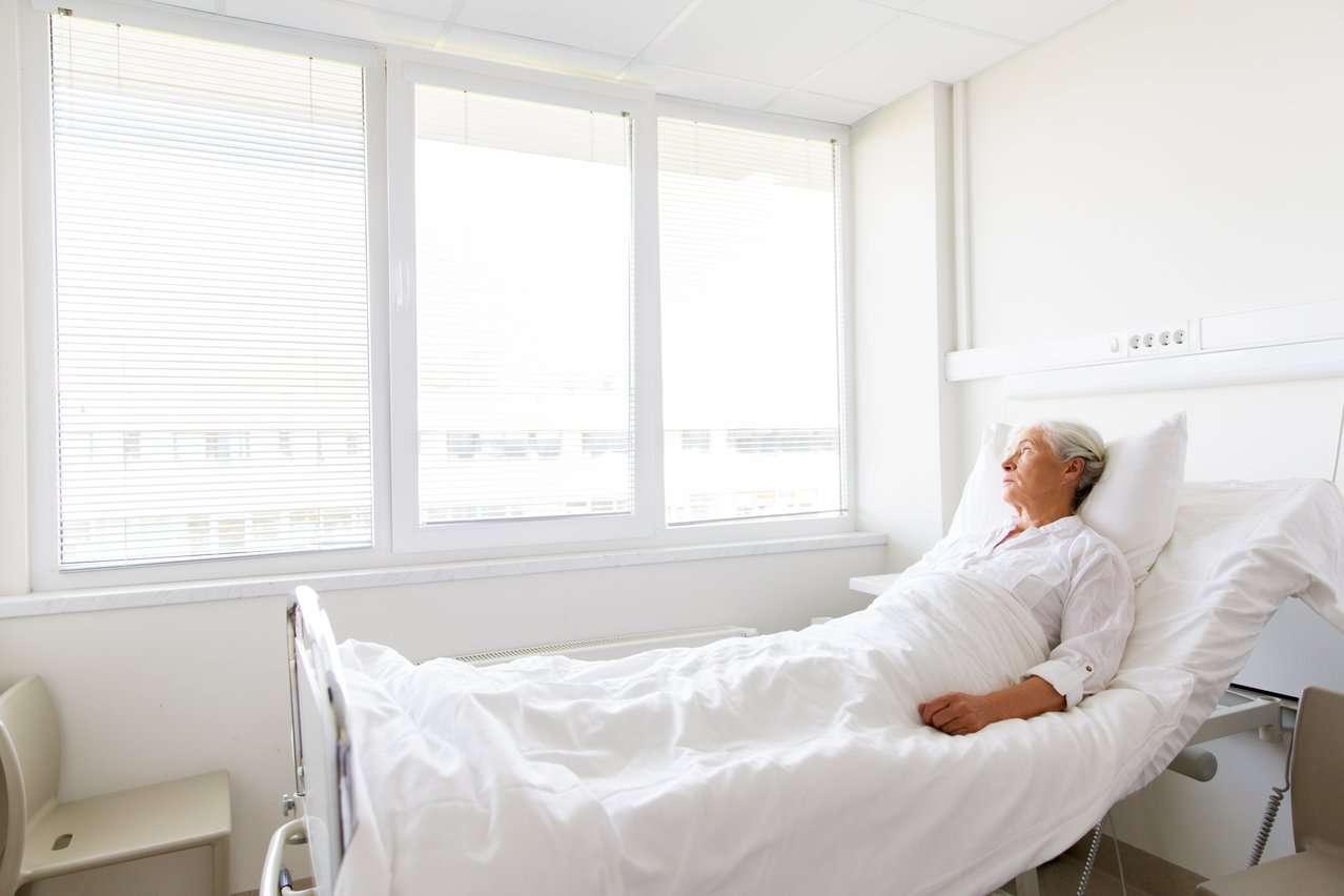 Kvinne ligger på sykehus. Foto