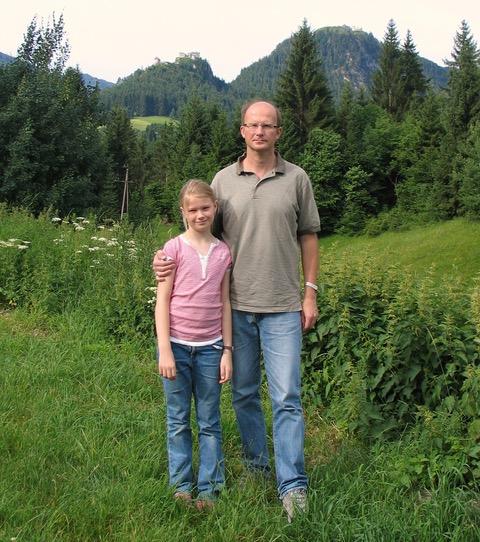 Jente med far i sommereng. Foto.