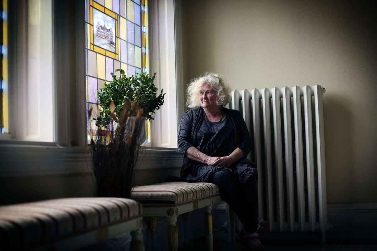 Kvinne i et hjørne av et rom. Foto.
