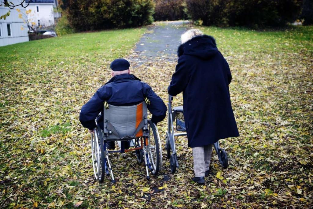 Mann i rullestol og kvinne med stokk. Foto.