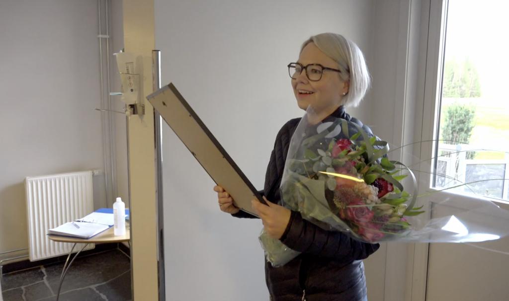 Kvinne med diplom. Foto fra video.