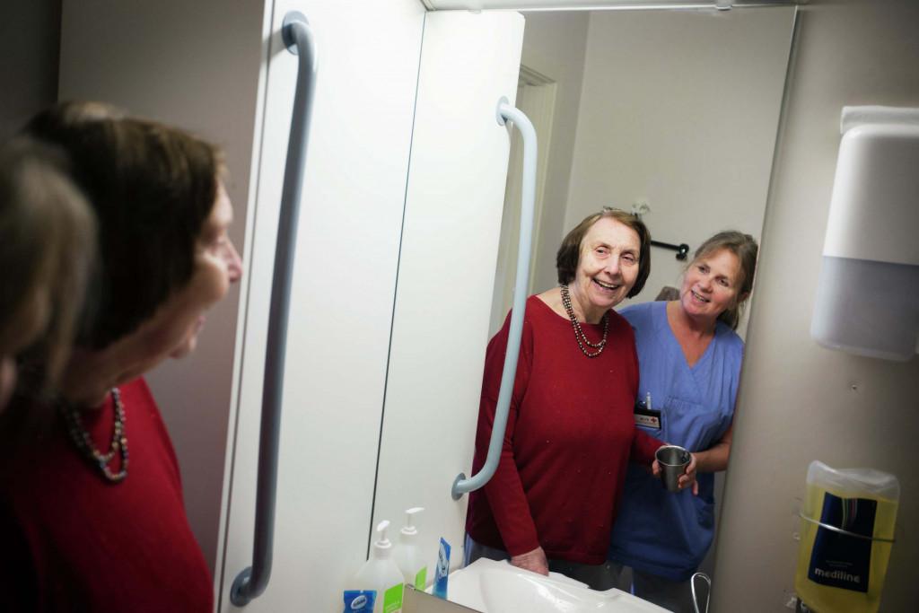 Kvinne og kvinnelig pleier ser seg selv i speilet. Foto.
