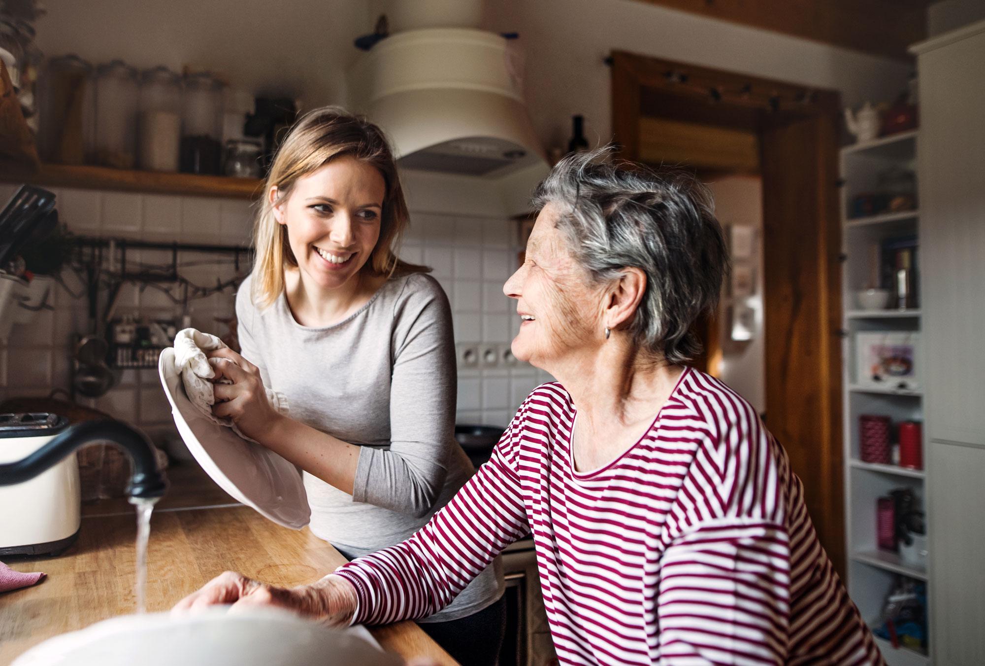 Eldre dame og yngre dame tar oppvasken